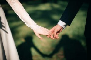 Couple holding hands on wedding day