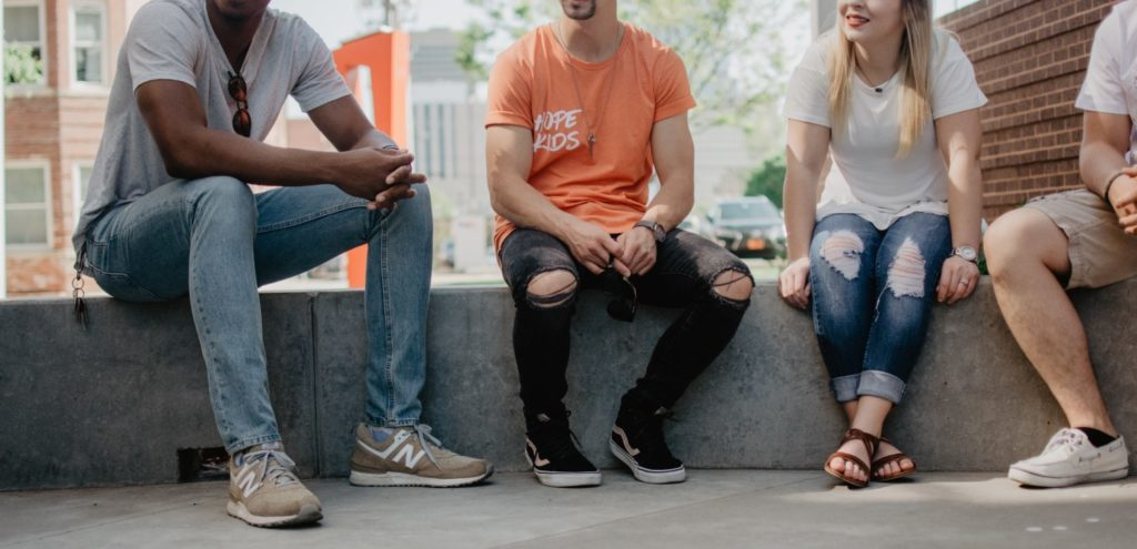 A group of people sat on a wall listening intently to someone out of frame.