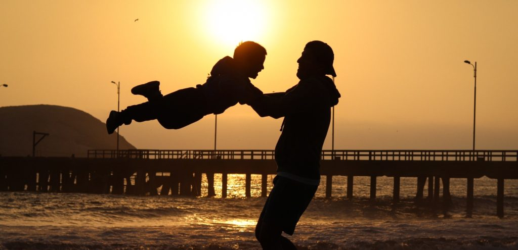 A father playing with his child on the beach during sunset.