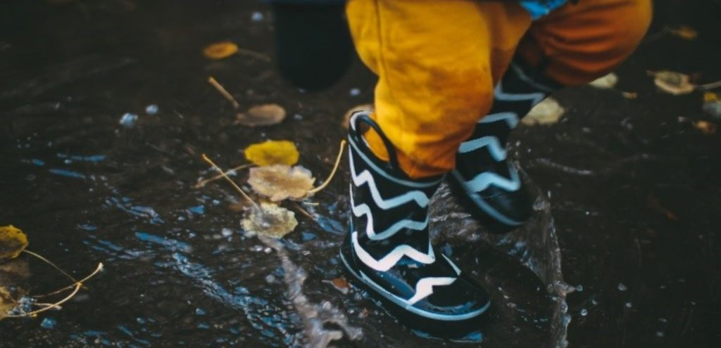 A toddle wearing wellies and jumping in a puddle.