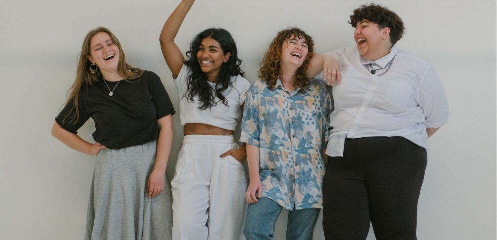Four women laughing whilst posing for a photograph