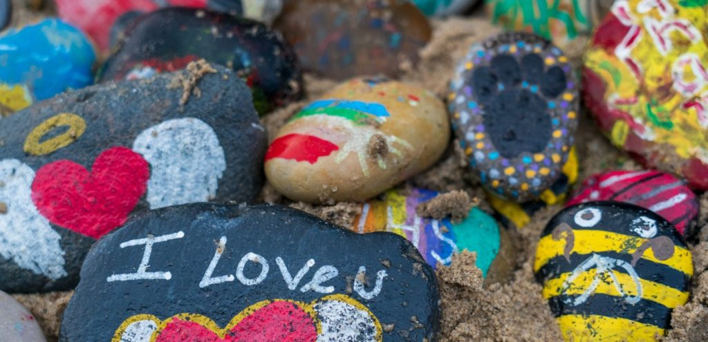 Pebbles covered in painted with colourful designs.