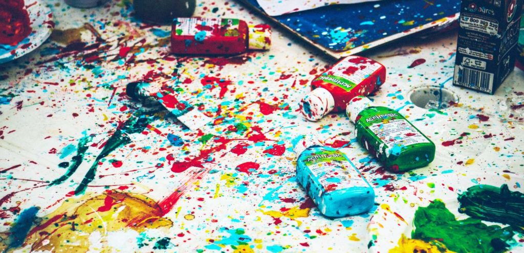 A messy table full of paint